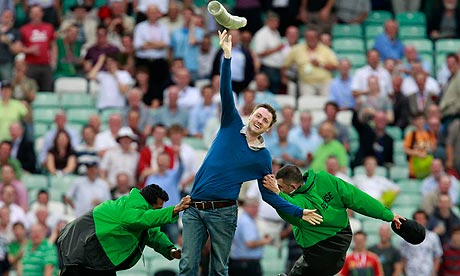 A spectator throws a stack of plastic drinks cups up in the air as he is tackled by security workers