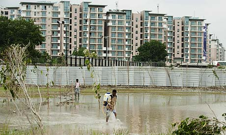 An Indian worker sprays pesticide to kill mosquitoes outside the Commonwealth Games athletes village