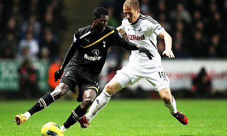 Emmanuel Adebayor, left, takes the ball past Garry Monk during Swansea's 1-1 draw with Tottenham