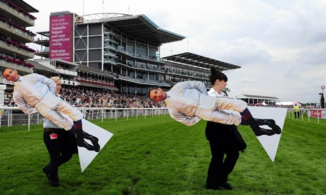 Cardboard images of Frankie Dettori are carried across York racecourse