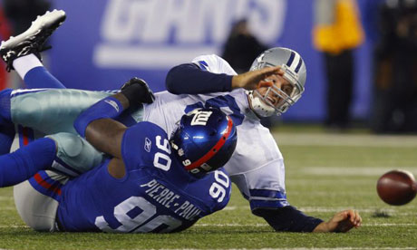 Dallas Cowboys QB Tony Romo is tackled by New York Giants' Jason Pierre-Paul