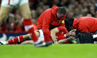 Wales's Jamie Roberts is treated on the field after a clash of h