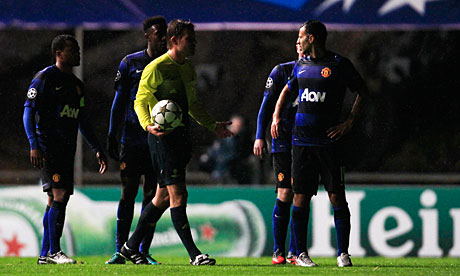 Manchester United players surround the referee Felix Brych after the power cut