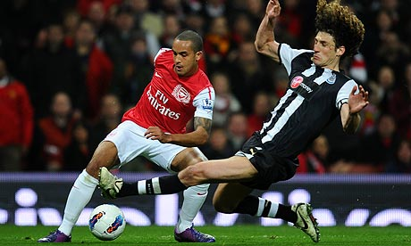 Arsenal's Theo Walcott tries to evade Fabricio Coloccini of Newcastle