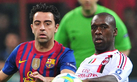 Barcelona's Xavi Hernandez  fights for the ball with AC Milan's Clarence Seedorf