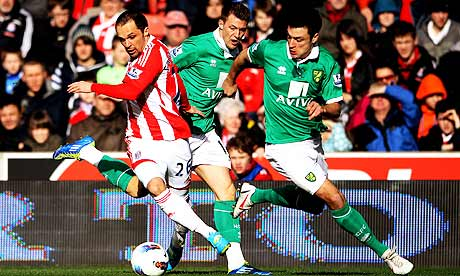 Matthew Etherington of Stoke City, left, evades Anthony Pilkington, centre, and Russell Martin