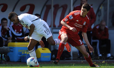 Liverpool's Martin Kelly competes for the ball with Swansea's Scott Sinclair