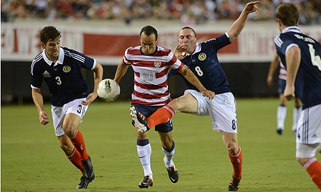 Unites States' Landon Donovan with Scotland defenders Charlie Mulgrew and Scott Brown