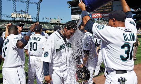 Seattle Mariners pitcher Felix Hernandez, center, is doused with water by Miguel Olivo