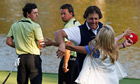 Phil Mickelson hugs his wife, Amy, on the 17th green as Rory McIlroy and Graeme McDowell look on