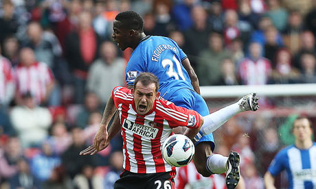 Steven Fletcher, below, feels the force of a tackle from Wigan's Maynor Figueroa