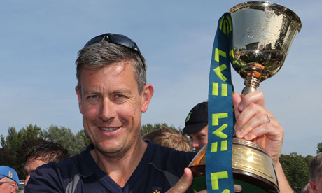 Warwickshire's director of cricket, Ashley Giles, celebrates with the county championship trophy
