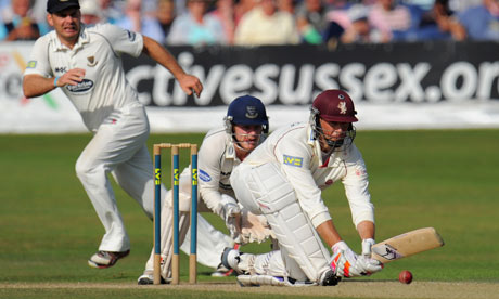Somerset's Marcus Trescothick sweeps as Sussex wicketkeeper Ben Brown looks on at Hove