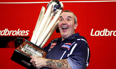 Phil Taylor with the winning trophy after becoming the world darts champion for a 16th time