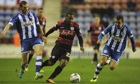 QPR's Junior Hoilett is pursued by two Wigan players at the DW Stadium on Wednesday.