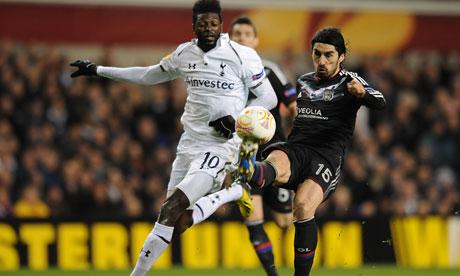 Tottenham's Emmanuel Adebayor and Lyon's Milan Bisevac battle for the ball.