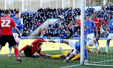 Cardiff City's Aron Gunnarsson, third left, scores against Peterborough in the Championship