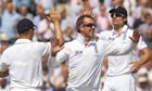 England's Graeme Swann celebrates the wicket of David Warner with Alastair Cook and Jonathan Trott.