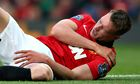 Manchester United's Phil Jones grimaces as he clutches his injured shoulder.