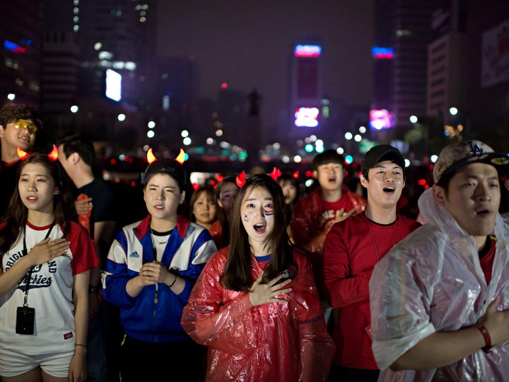 South Korean football fans sing their national anthem