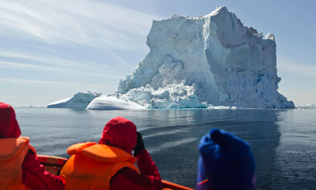 Tourists sit in a boat near a giant iceberg in Greenland