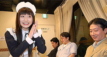 A woman in a maid costume serves customers in Tokyo