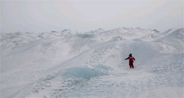 A person walking over a snow-covered Kangerlussuaq, Greenland