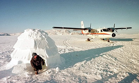An Inuit child climbs out of an iglu on an ice floe in the Opingivik area of Baffin Island