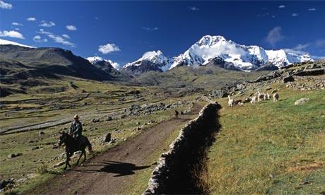 A Quechua farmer rides on a horse at the foot of Ausangate Mountain, Cuzco, Peru