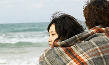 Couple at the beach wrapped in a blanket