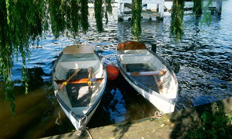 Two wooden rowing boats moored at the side of the River Thames near Cookham