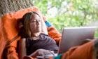 Woman using laptop in a hammock