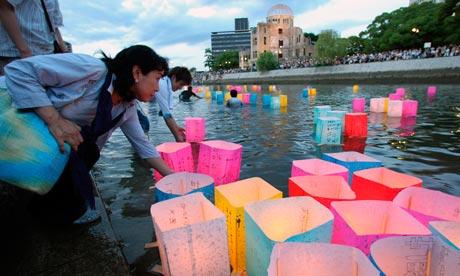 Candlelit lanterns float on the Motoyasu River