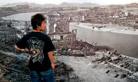 A Japanese man looks at an archive photograph of the US atomic bombing of Hiroshima