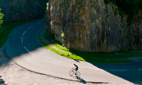 A lone cyclists climbing the road through dramatic Cheddar gorge on a fine sunny summer morning