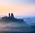 Corfe Castle shrouded in mist at sunrise, Dorset