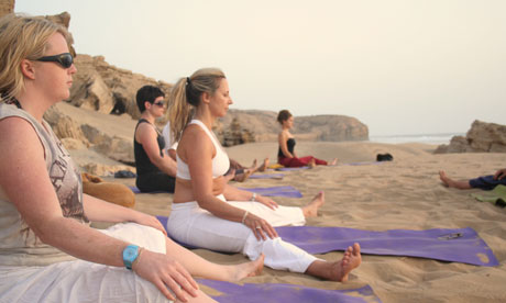 Practising yoga on the beach at sunset on the Morocco trip
