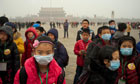 Children wear masks as a thick haze of air pollution envelopes Tiananmen Square in January.