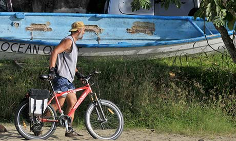 Man with bike on beach in Tobago.