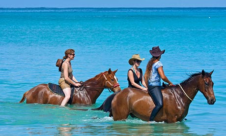 Horseriders in the sea at Buccoo Bay, Tobago.
