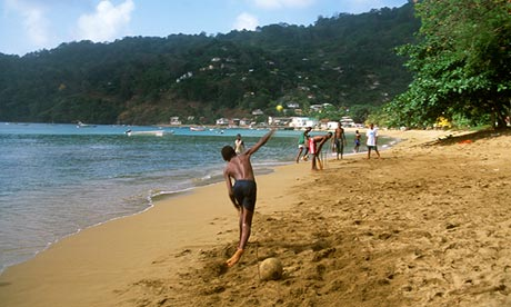 Tobago boys playing cricket on the beach.