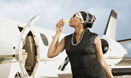 A woman drinks champagne outside an airplane