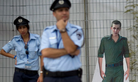 Israeli police officers stand guard in front of a cut-out of captured Israeli soldier Gilad Schalit,