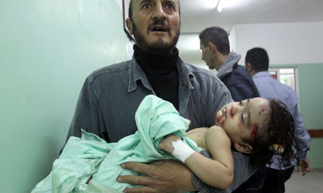 A Palestinian man carries a wounded child at a hospital following an Israeli air raid in Beit Lahia in the northern Gaza Strip, on November 17, 2012. Photograph: Moiz Salhi/AFP/Getty Images