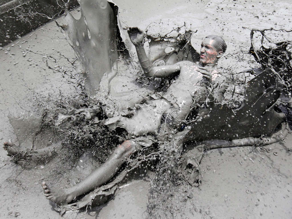 A foreign tourist plays with mud during the 13th Boryeong Mud Festival