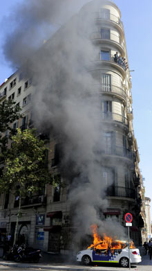 A police car burns in central Barcelona during general strike