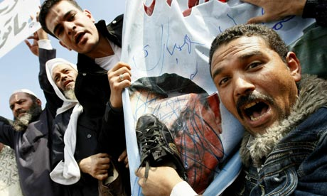An Egyptian demonstrator hits Mubarak portrait with a shoe