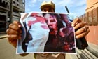 A picture of a dead Muammar Gaddafi is held up by a fighter in Tripoli