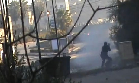 A Syrian rebel fighter fires a rocket propelled grenade at an armoured vehicle in Homs
