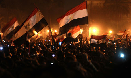 Egyptian anti-government protesters wave flags as they celebrate in Tahrir Square